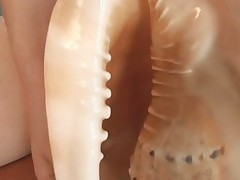 Crazy Alice enjoys using a sea shell on her pussy